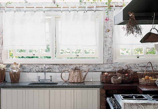 As paredes são de tijolos de demolição e madeiras lavadas, com acabamento em pátina branca. O teto, de forro aparente, foi pintado e acima da bancada da pia há um telhado de vidro, que proporciona maior claridade para a área de trabalho  Arquivo / Casa e Jardim