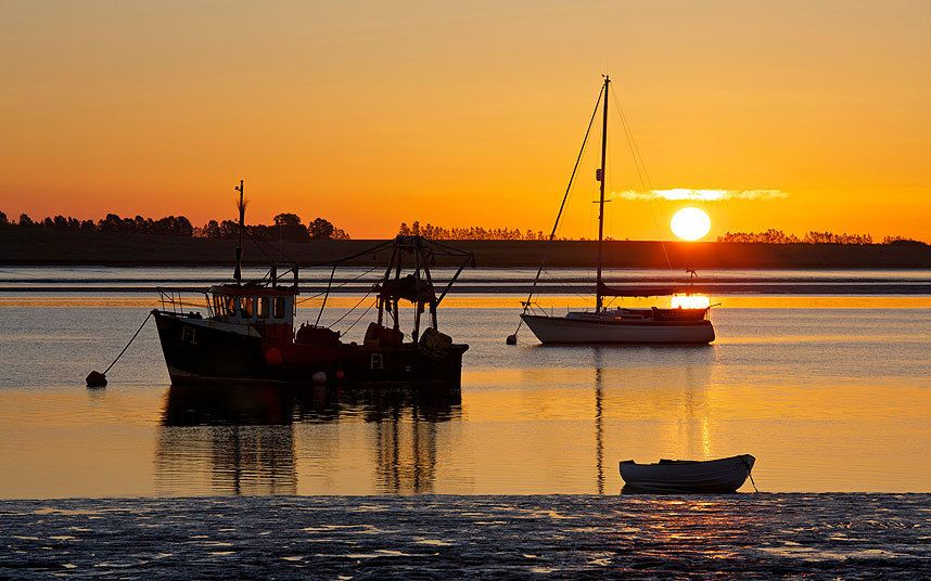 A gorgeous orange glow lights the scene as the sun rises into a clear, calm morning sky over boats moored in the Swale estuary near Harty Ferry on the Swale Estuary in Kent