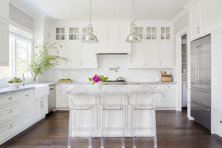 Kartell Ghost Counter Stools Sit At A White Kitchen Island Topped With Super Quartzite
