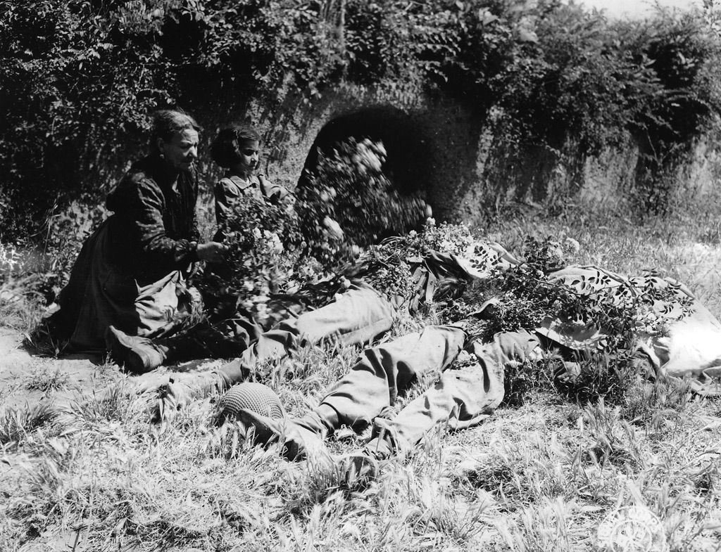 An Italian woman and a young girl cover dead G.I.s with cuttings from a rose bush on June 4, 1944, the day Rome fell.