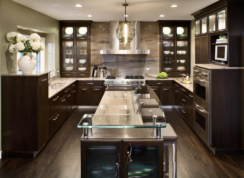 Deep chocolate brown cabinets with crown molding add a traditional touch to this contemporary kitchen design glass cabinetry inserts and a glass bar top