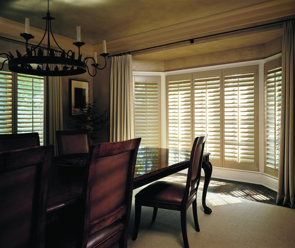 Classic plantation shutters in a bay window in a traditional dining room.