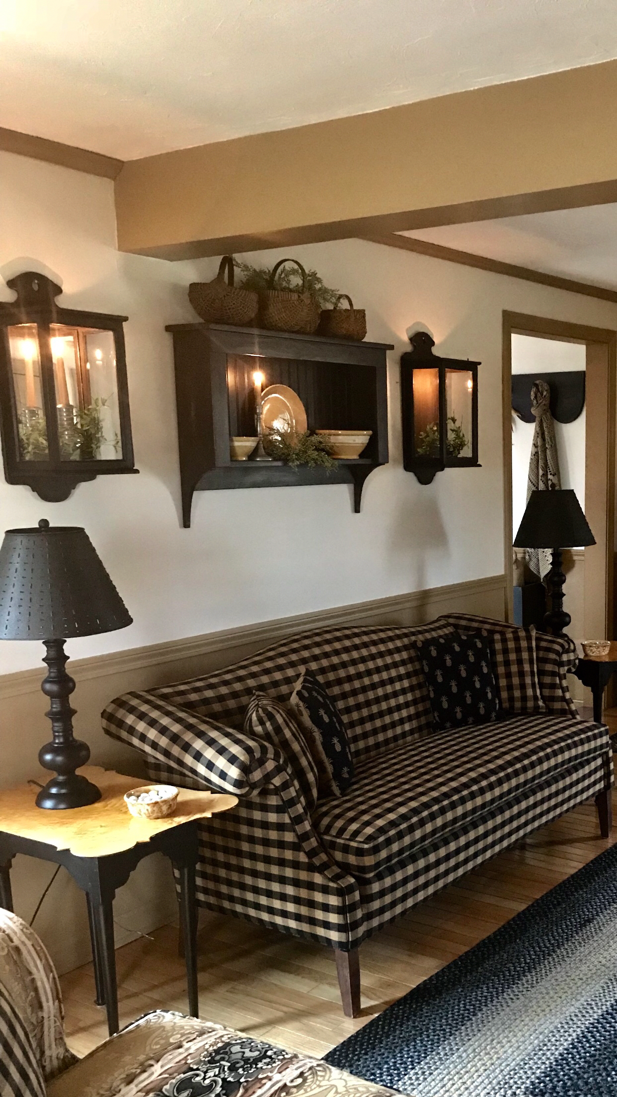 sconces and SHELF above couch And black and white cream plaid or