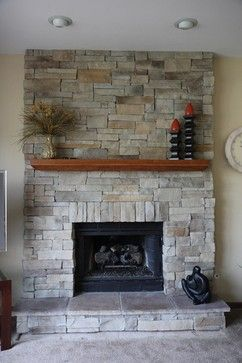 Stacked Stone Fireplace With A Simple Mantle For A Plant