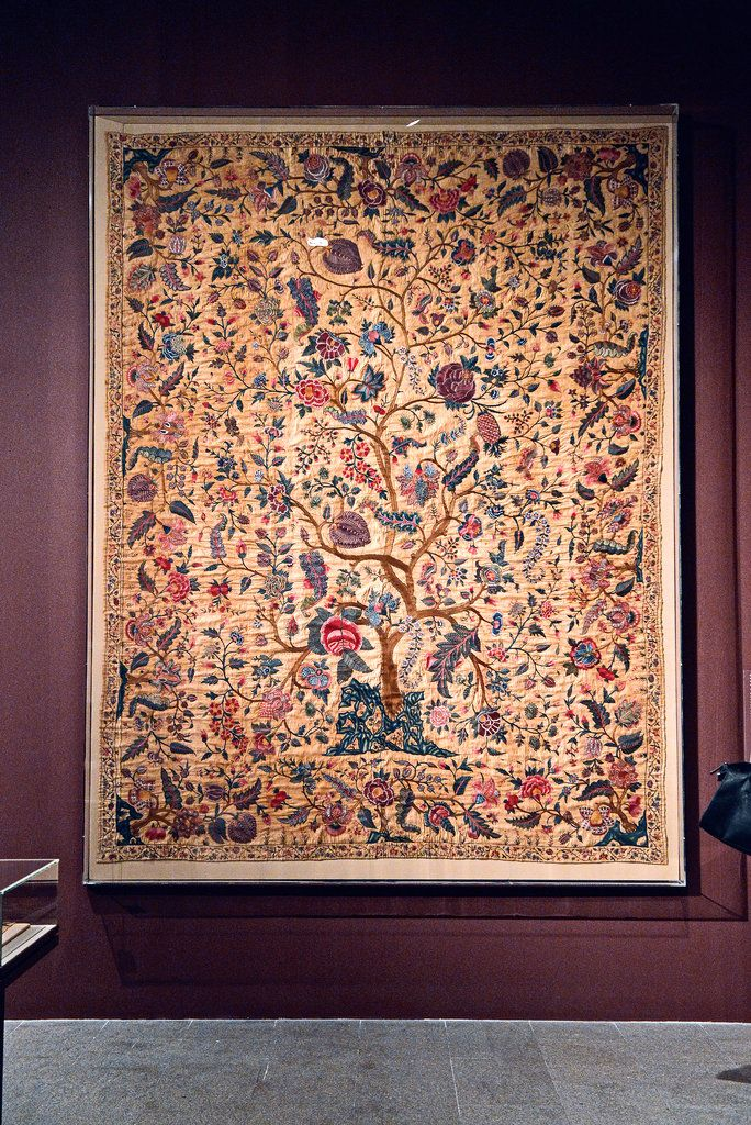 "An 18th-century Indian palampore, or wall hanging depicting a tree of life surrounded by scrolling vine-and-flower patterns. The palampore is a leitmotif in several galleries in the show, Ms. Smith writes, with versions in embroidered or dyed cotton inspiring textile producers around the globe.  ""The Indian genius for elaborate dying and painting processes was a particular challenge to equal,"" she notes.  Philip Greenberg for The New York Times"