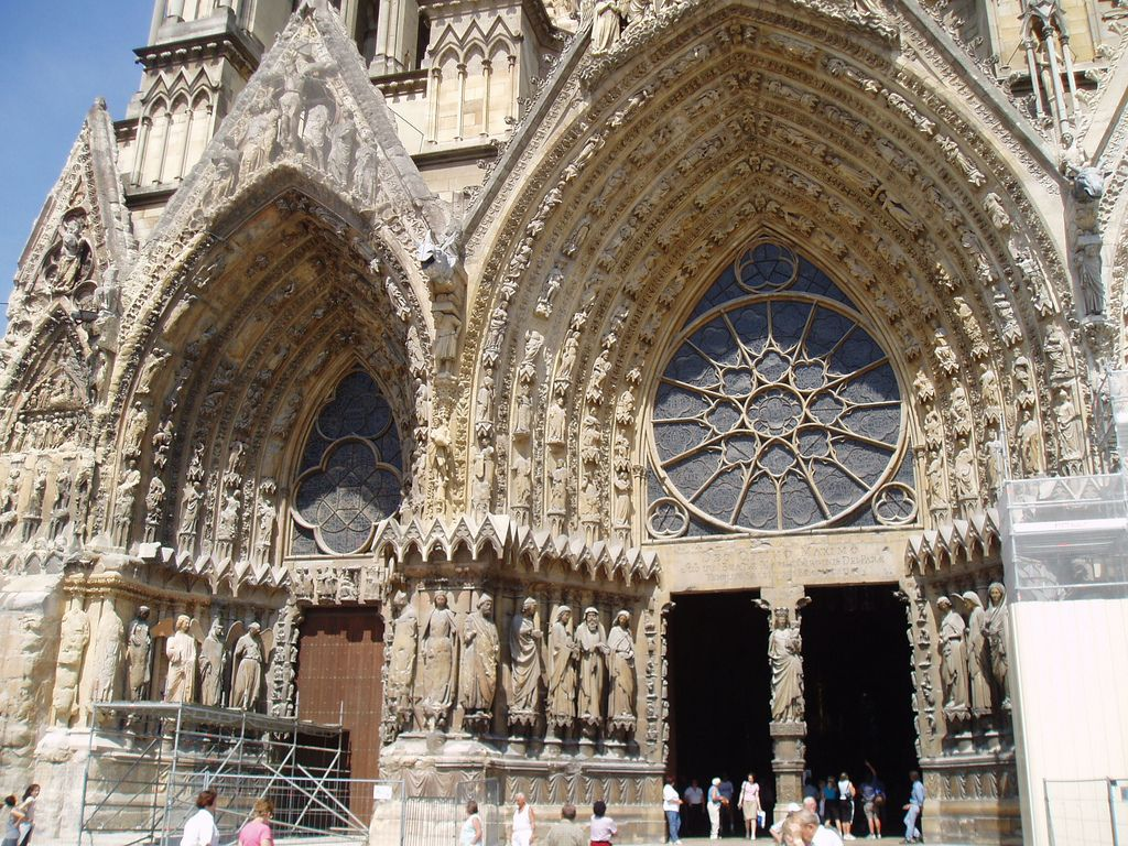 https://flic.kr/p/7vsrSF | Portals of West Facade, Reims | Reims Cathedral, coronation church of the French kings and one of the finest gothic structures ever built. It's vast scale, masterful design and rich sculptural adornment are virtually without equal.   The west facade is one of the most celebrated achievements of medieval architecture. Beautiful sculptures from the 13th & 14th centuries adorn the three main portals  and include such famous figures as the 'Smiling Angel of Reims' and…