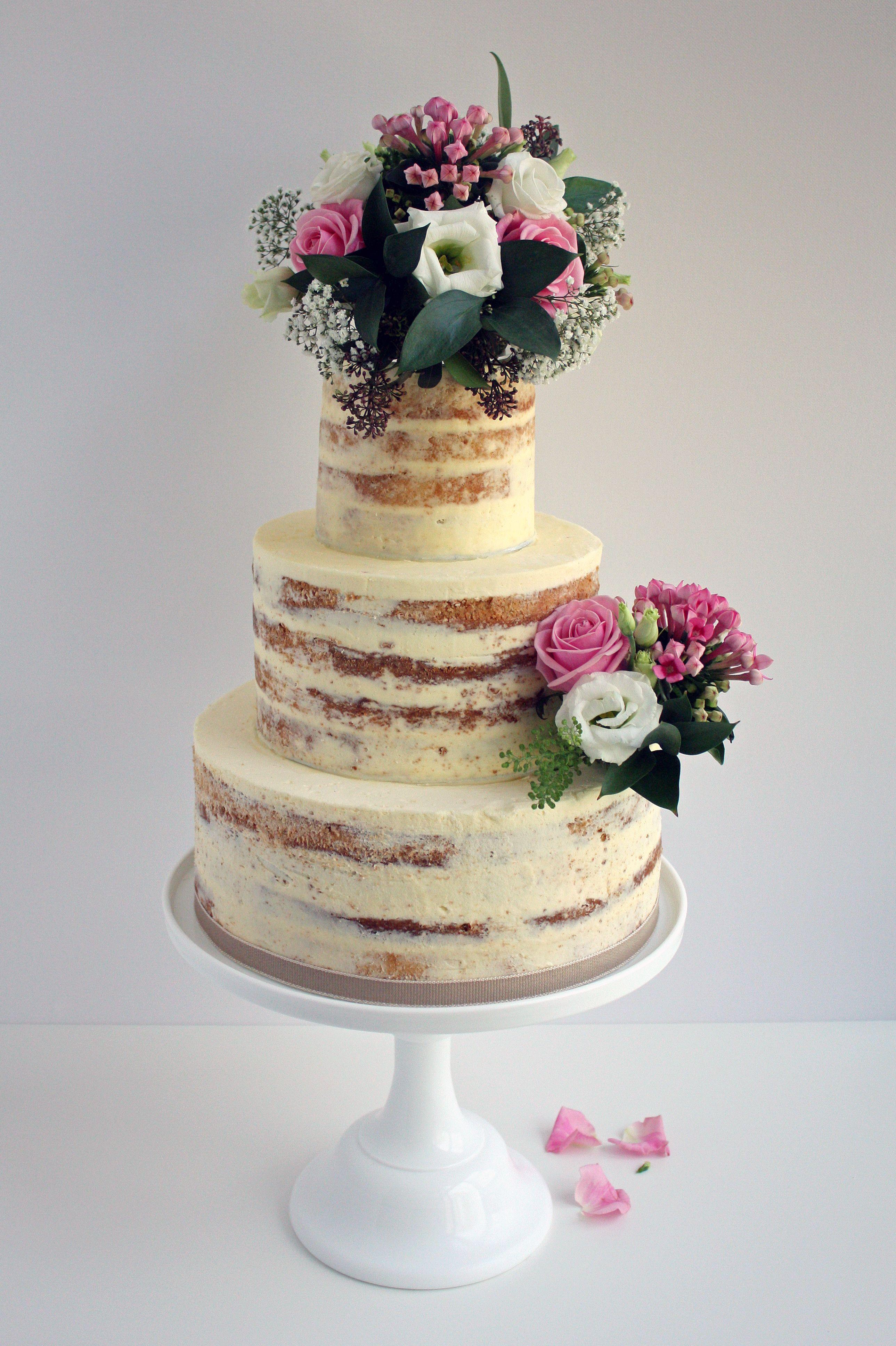 Beautiful three tier semi naked buttercream wedding cake decorated with fresh flowers