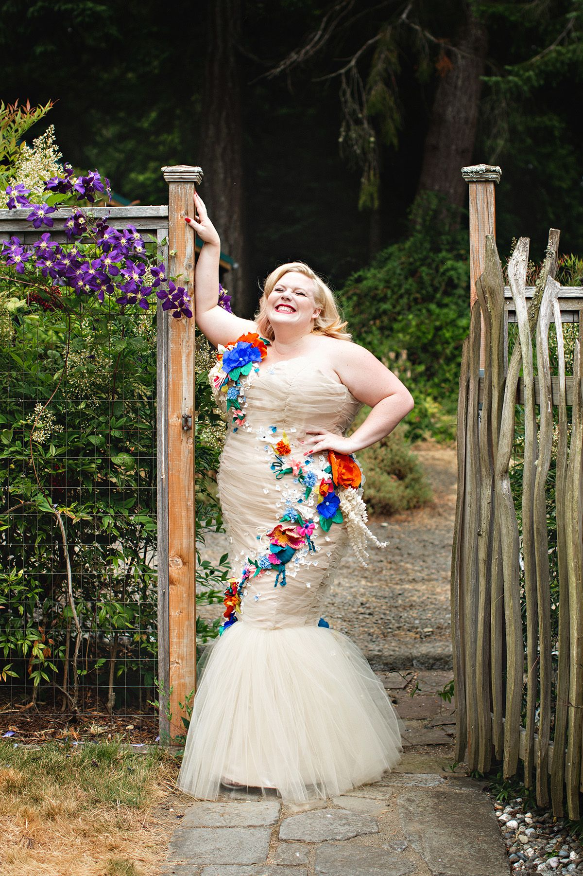 Lindy West smiling in her strapless mermaid gown by a garden fence | A  Practical Wedding