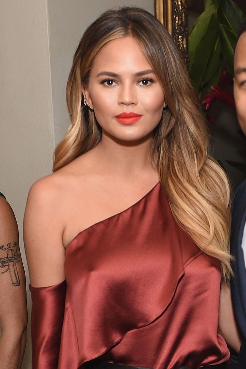 Who: Chrissy Teigen What: Red Hot How-To: Sometimes it's cooler to go off script and play with different shades and textures of the same color. Teigen paired a shiny burnt red silk top with matte coral lipstick for a subtly striking look that works for day or night.  Editor's Pick: YSL Rouge Pur Couture Satin Radiance Lipstick in Rouge Rose, $36, sephora.com.   - HarpersBAZAAR.com