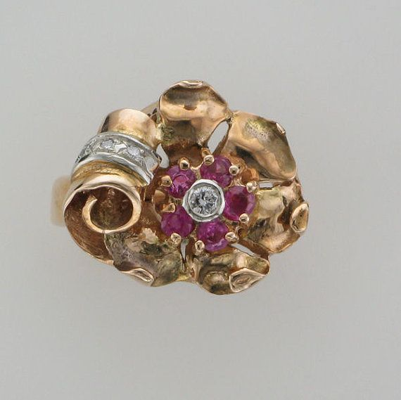 Ladies 14 karat yellow and rose gold ruby and diamond ring contains one full cut diamond set in the center of a flower design. The full cut