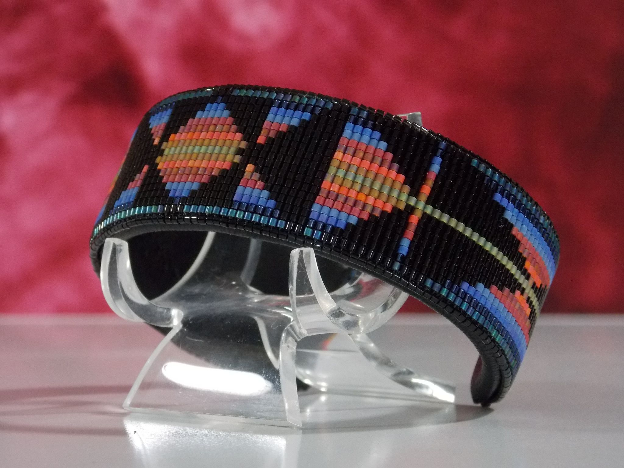 This American Indian beaded bracelet In A Southwestern Sunset Pattern With The Colors Of Black and Soft Sunset Colors by LJ Greywolf The base used for this bracelet is copper wrapped in a soft buckski