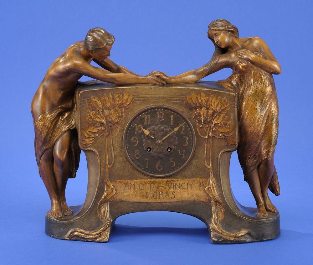 Tischuhr von Goldscheider Wien um 1900 Bezeichnet: Amicita-vincit Horas. Messingwerk mit Schlag au — Porzellan