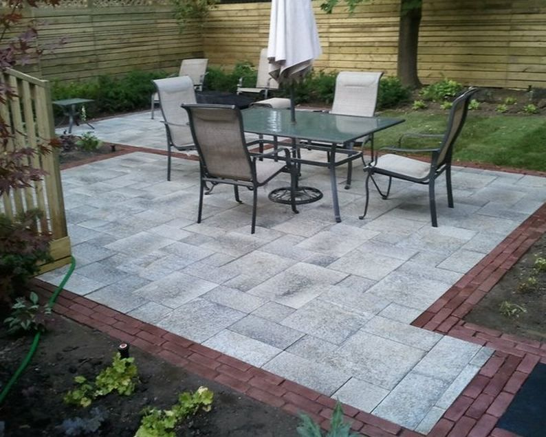 use a wind break wall to shield against windy weather geometric patio space stone patio designspatio - Stone Patio Designs