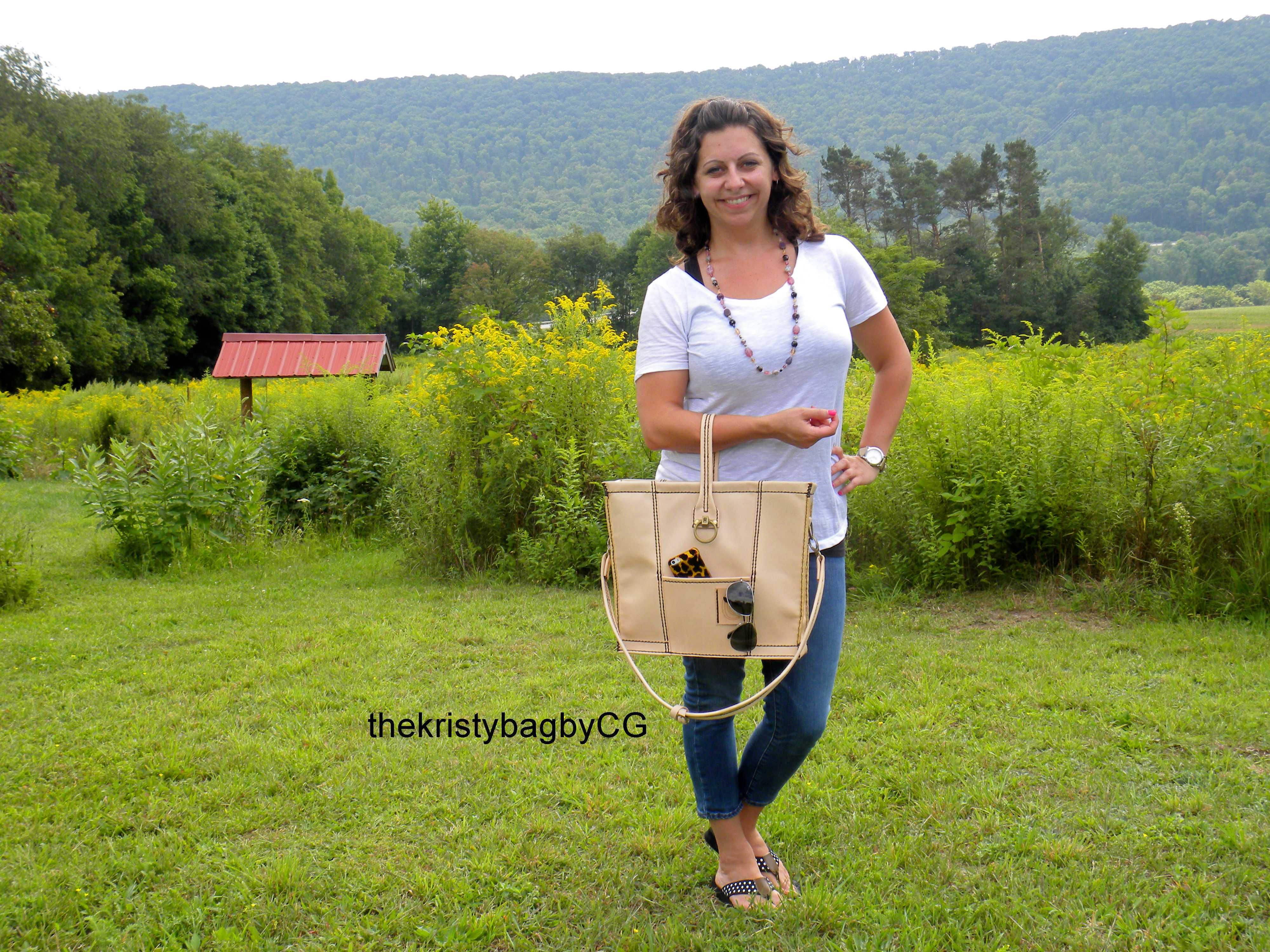Trend setting handbag designer Kristy Lash  Handbag Hottie strikes a pose with tote bag in goldenrod field at Crabtree Gardens The Kristy Bag by CG