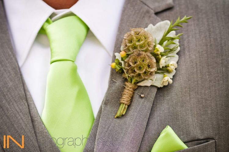 Groom's Boutonniere was made of dusty miller, wax flower, scabiosa pods, and peach hypericum berry. Tied in twine.