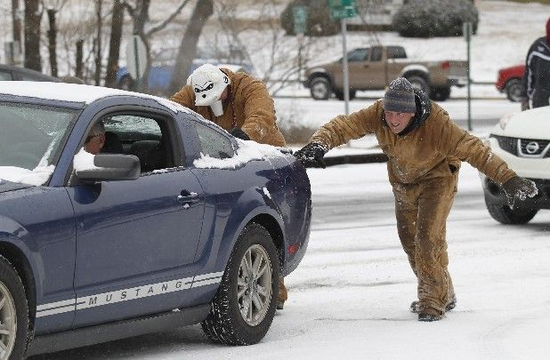 Jon Overcash, left, and teacher Chad Burnette push a Mustang up the snow-covered Dallas Road in front of Chattanooga High School Center for ...