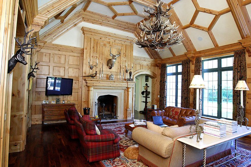 Living room with paneling, vaulted ceiling, Tudor arch fireplace and plaid chairs - Fusch Architects