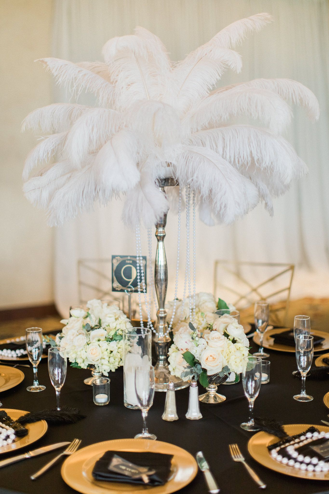 Tall centerpieces of feathers draped with pearls surrounded with ...