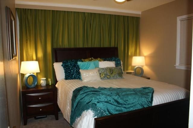 Get rid of off centered windows by hanging curtains behind bed