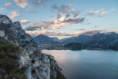Riva del Garda, Lake Garda, Moving Clouds, Trentino-Alto Adige, Northern Italy, Sunset, Dusk, Blue Sky, Alps, Evening, Rock (Geology), Non Urban Scene, Mountain Region, Travel Destination, Mountains, City, No People, Body of Water, Sunshine, Europe (Continent), Stock Footage,