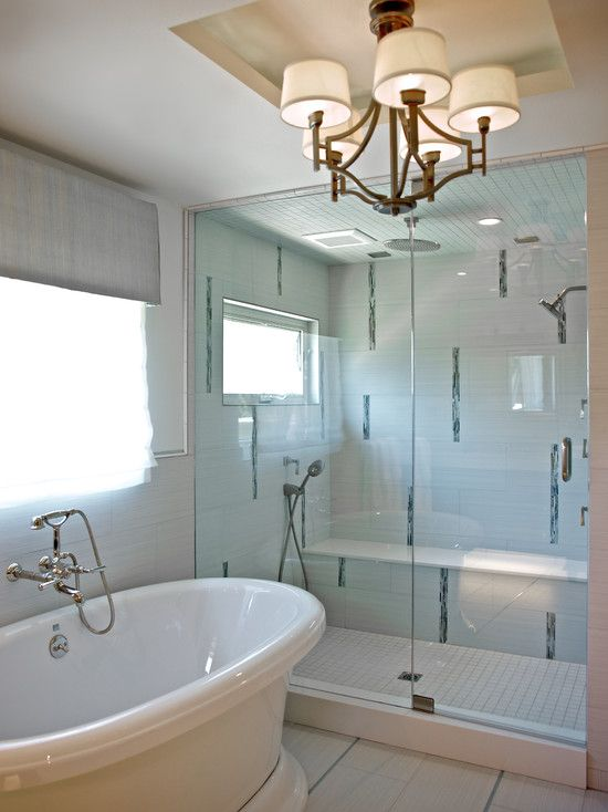 bathroom with floor inlaid with glass, floating cabinets, a deep ...