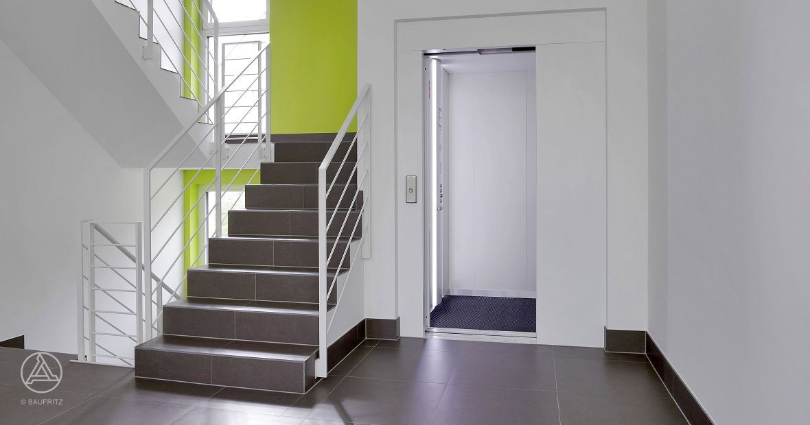 moderner aufzug mit integrierter leuchts ule sowie gro es und helles treppenhaus baufritz. Black Bedroom Furniture Sets. Home Design Ideas