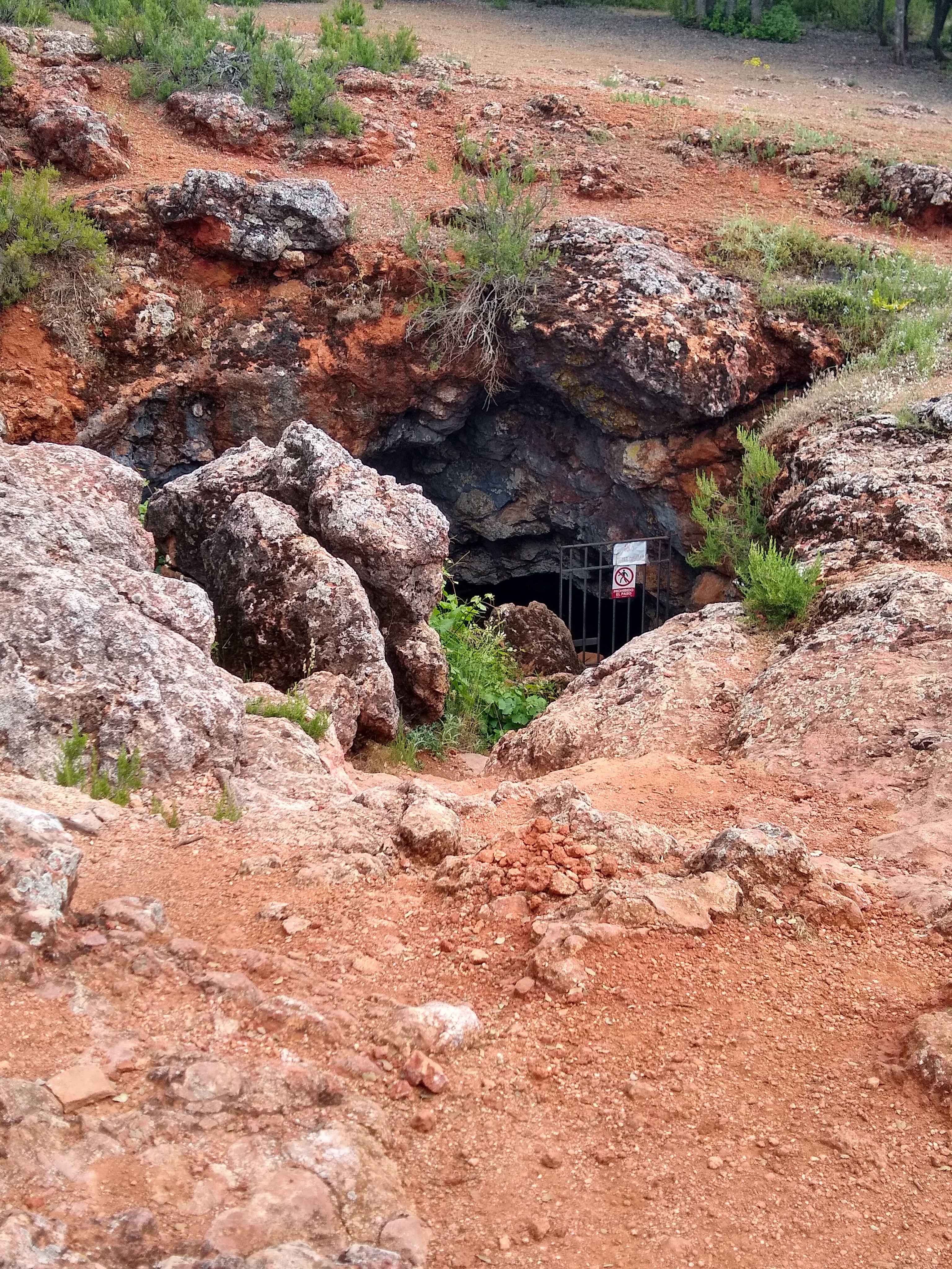 Una sima oscura se abre en mitad de una zona de tierras rojas. Estamos ante la cueva de Montesinos