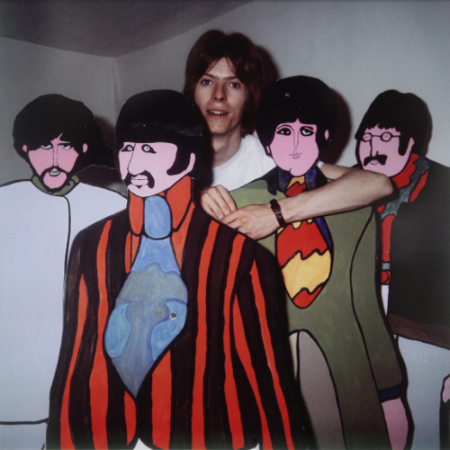 """David Bowie with cutouts of the Yellow Submarine Beatles, photographed by Phil Velasquez/Chicago Tribune.  """"I just met David Bowie [during the Dark Horse Tour]…. David Bowie, these were my very words, and I hope he wasn't offended by it because all I really meant was what I said. I pulled his hat up from over his eyes and said: 'Hi, man, how are you, nice to meet you,' pulled his hat up and said, you know, '"""