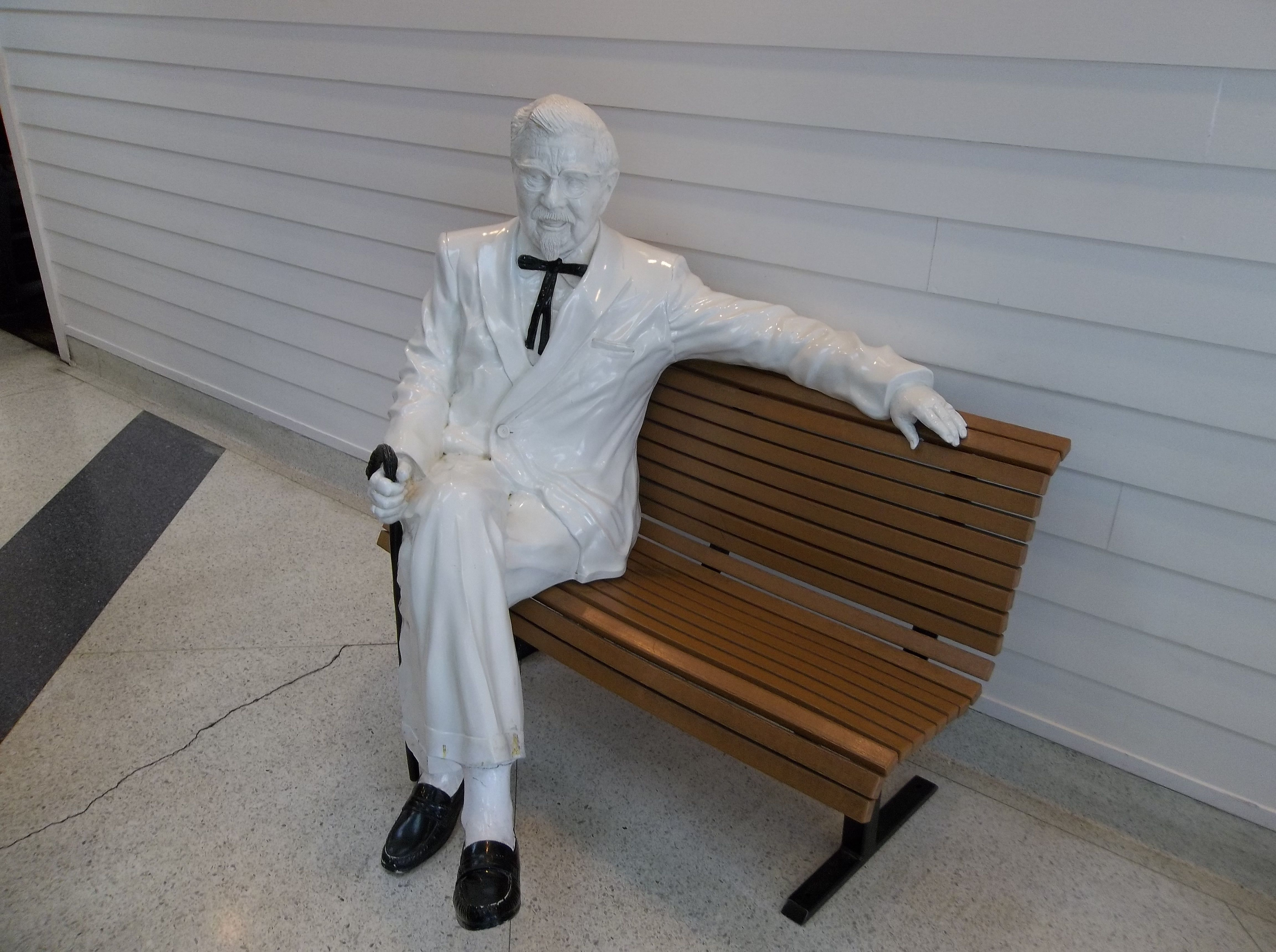 Colonel Sanders Statue On A Bench Inside The Birthplace Of