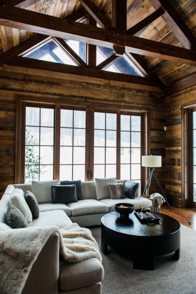 Modern cabin living room with gray sectional, mixed velvet accent pillows and a glossy black coffee table.