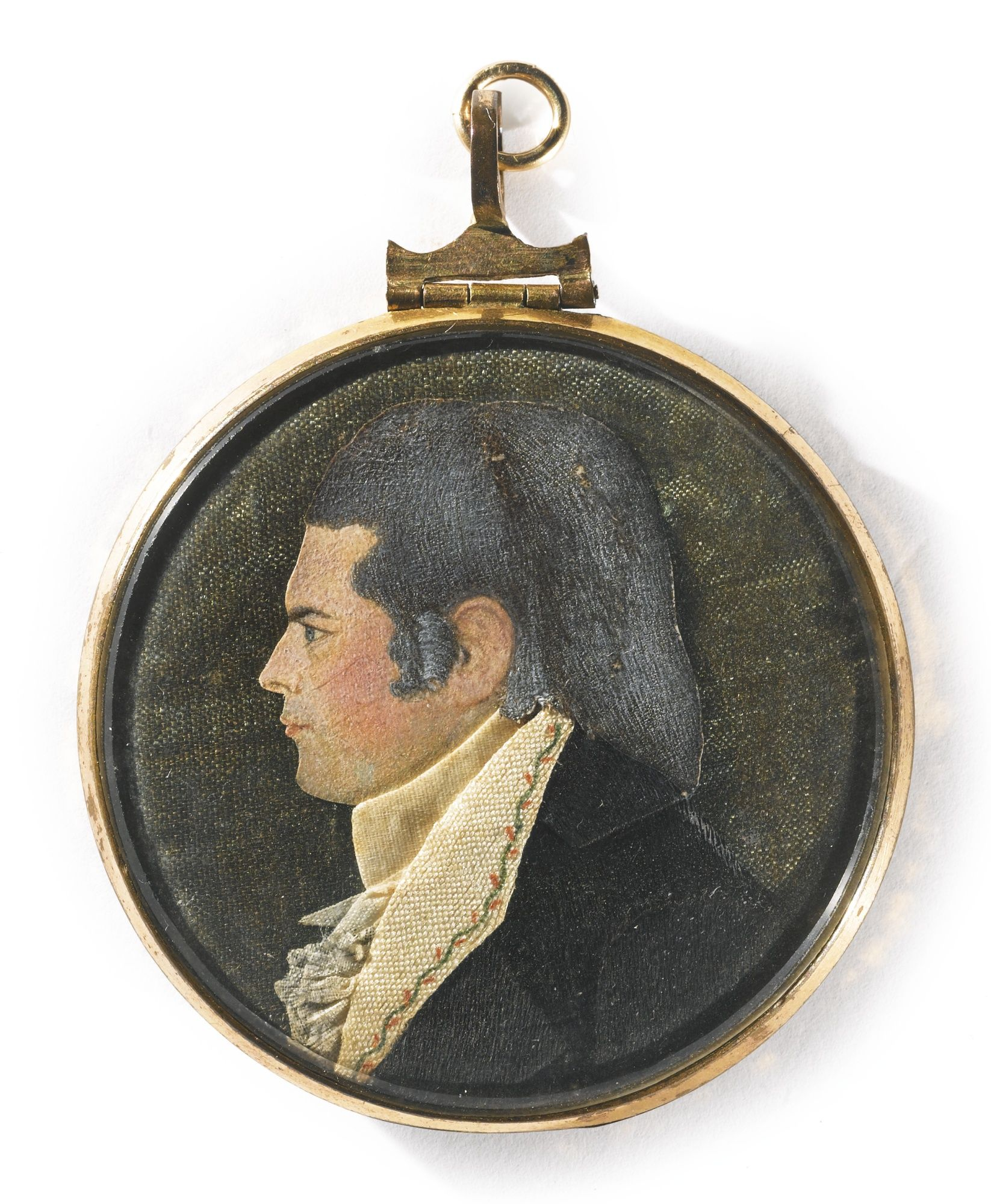 """A """"Dressed"""" Miniature Portrait of a Gentleman by Mary B. Way (1769-1833), New London, Connecticut, circa 1800 - A """"dressed"""" miniature profile bust portrait of a rosy-cheeked young man, of appliquéd fabric, the reverse with a watercolor of a lady standing beside a monument, in a circular gold-metal locket frame with a painted glass mat in gold, black and white enamel.  Diameter 2 inches; 2 1/8 by 1 7/8 inches."""