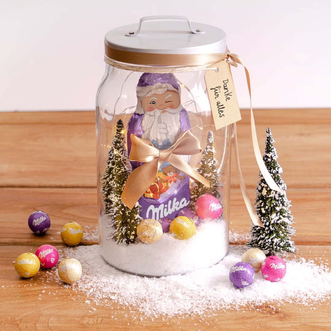DIY: Milka Weihnachten im Glas #laternebasteln Weihnachten ist die Zeit, etwas zurückzugeben. Das geht am besten mit dieser Geschenkidee: Milka Weihnachtsmann im Glas. Diese schokoladige DIY Weihnachtsdeko ist ganz einfach & schnell selber gebastelt. Wem möchtest du etwas zurückgeben?   Du brauchst: 1 Glas ca. 30cm hoch, 1 Milka Weihnachtsmann 100g, Milka Weihnachts-Kugeln, kleine Dekotannenbäume, wiederverwendbare LED-Lichterkette, Kunstschnee, Schleifenband, Geschenkanhänger. #weihnachtsdekoglas