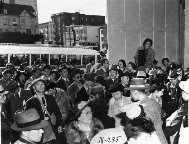 """Dorothea Lange, sullo sfondo, mentre documenta con la sua fotocamera la deportazione dei nippo-americani al campo """"di reinserimento"""" di Santa Ana, in California, nel 1942."""