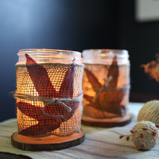 Mason jars decorated with burlap ribbon and fall leaves add a warm glow to the holiday table.
