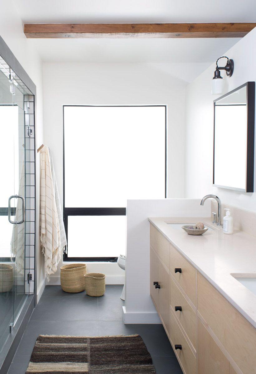 white bathroom black floor tile natural wood vanity