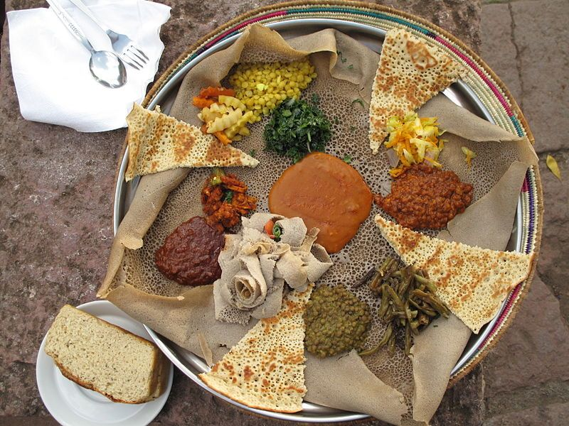 injera bread topped with several kinds of wat (stew), is typical of Ethiopian cuisine.