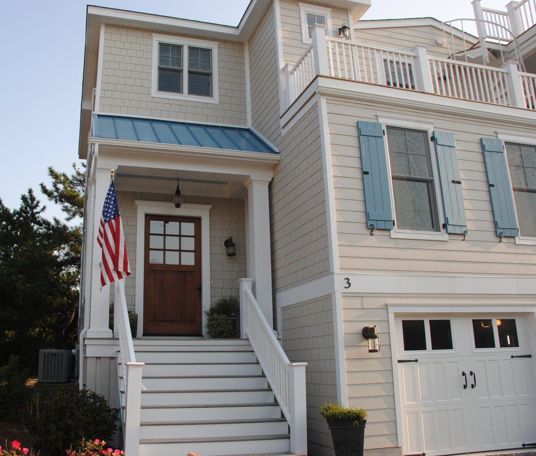 Beach house exterior blue metal room tan siding carriage door garage doors texas beach for Beach house exterior colour schemes