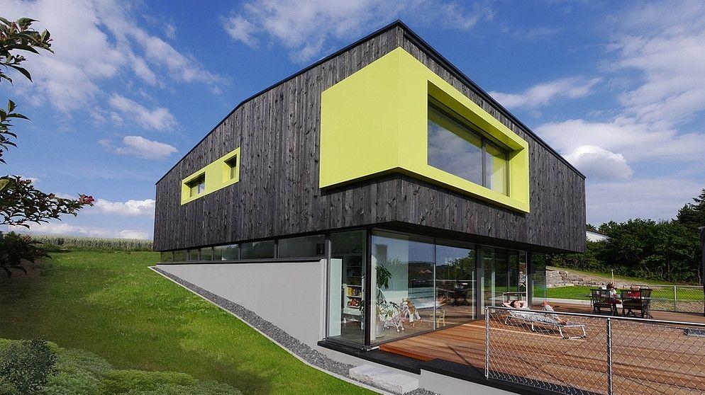 die gr ngelben fensterrahmen aus aluminium bilden einen markanten kontrast zur verkohlten. Black Bedroom Furniture Sets. Home Design Ideas