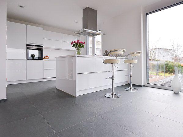 La cuisine blanche avec des éléments en métal sur en sol en ardoise