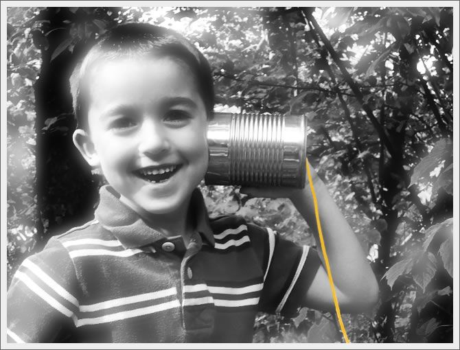 Boy listening to a tin can telephone.
