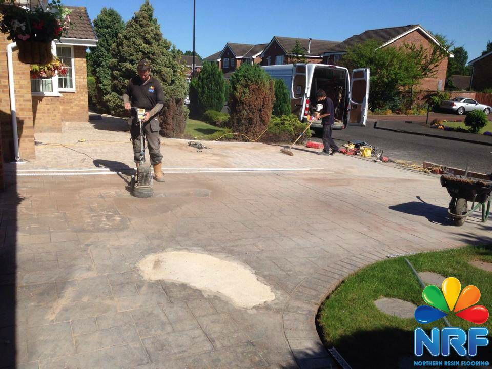 Northern Resin Flooring grinding back existing patterned concrete surface with Logo.