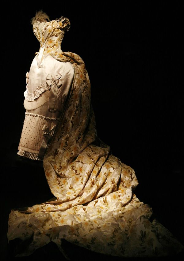 Charles Frederick Worth couture evening gown with bustle train and embroidered with metal glass sequin paillette from 1888. Made from pale pink silk and lace, the court presentation ensemble are sewn with pleat, ruffles and bow. House of Worth.