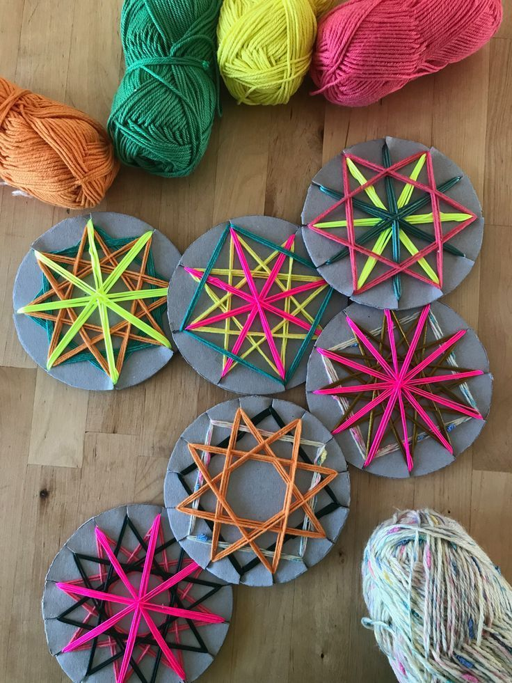 Colourful woven yarn star decorations. For lots of fun craft activity inspiration to make with your kids visit the Mini mad Things website.