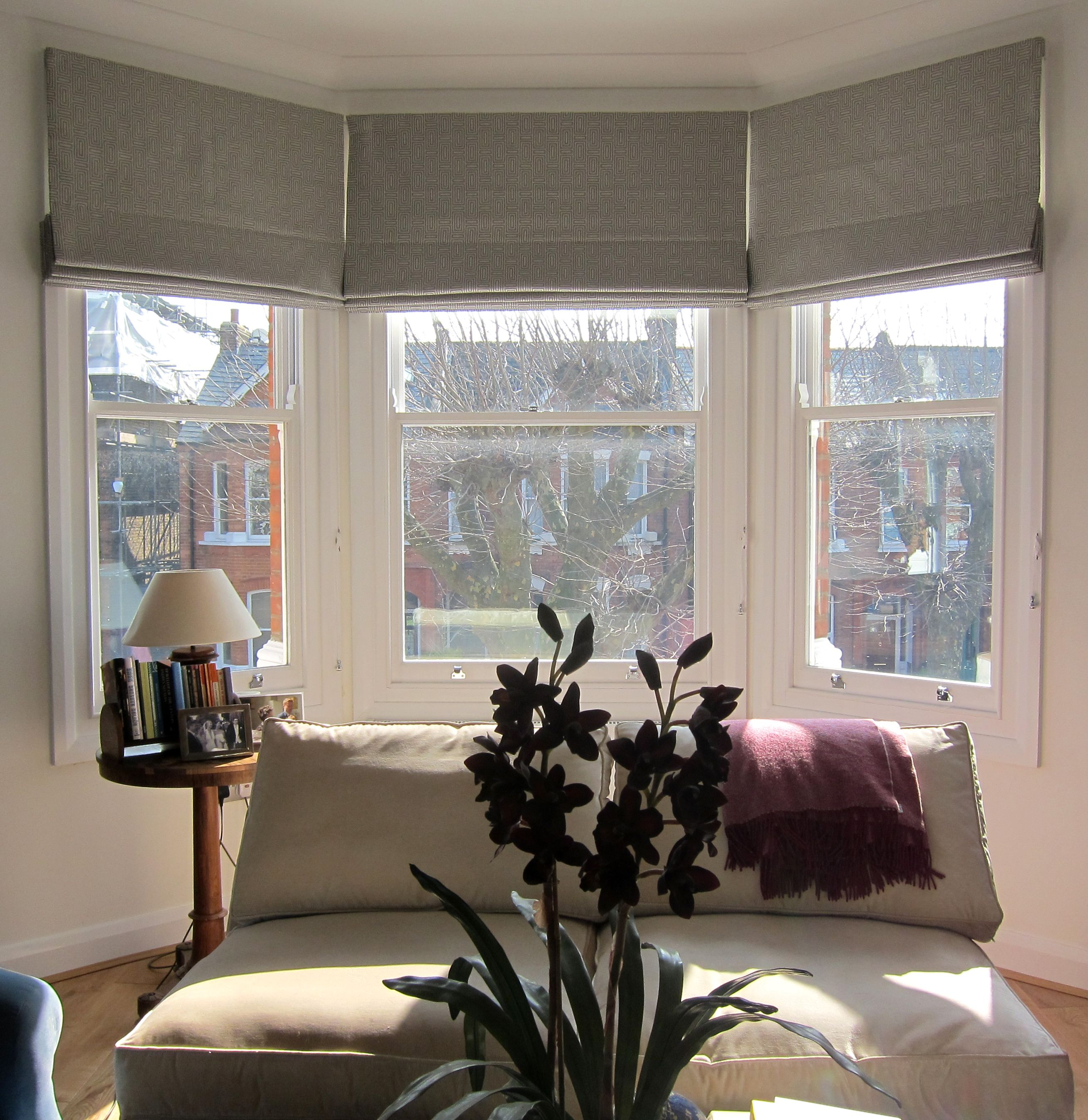 Geometric patterned roman blinds in a bay window could for Bedroom bay window treatments