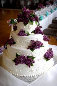 Wedding cake with plum colored flowers.