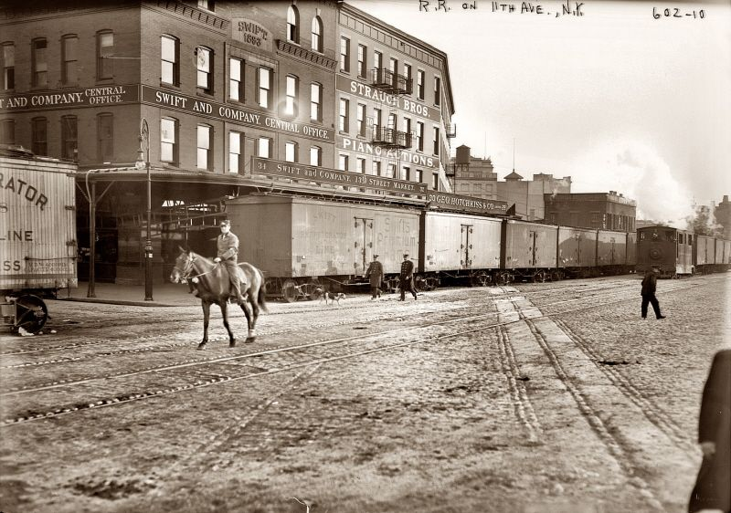 "New York Central Railroad - Meat Packing District - Eleventh* Avenue & West 12th Street - ca. 1911 Man on horse is a NYCRR Watchman / RR Policeman a/k/a ""West Side Cowboy"" escorting the locomotive as required by NY City law."