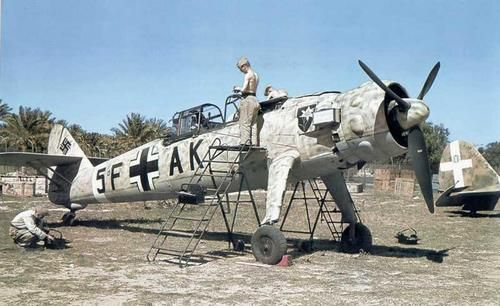 German mechanics working on disassembled recce plan Henschel Hs-126B of Luftwaffe's observation unit 2.(H)/14 on an airport on North African airfield employed also by Italian Air Force. Note indeed, in background, the tail of an Italian aircraft, perhaps a Caproni, 1942.