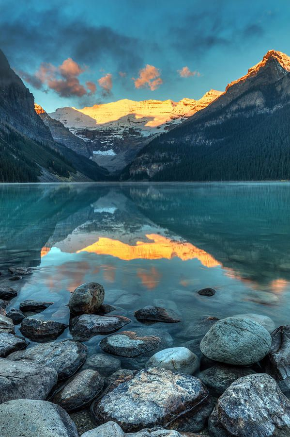 The sun rising and illuminating victoria glacier with a perfect reflection in the turquoise water of Lake Louise in Banff National Park, Alberta, Canada by Pierre Leclerc Photography