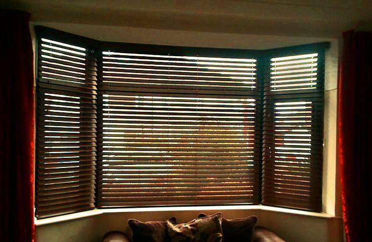 dark oak faux wood venetian blinds in a bay window from