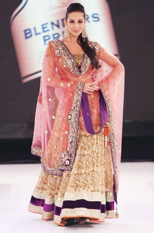 beautiful indian model wearing a gorgeous purple gold and cream lehenga choli